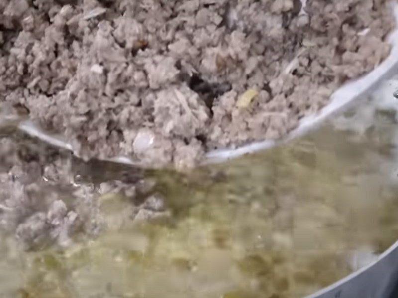 Cho phần thịt ếch đã xào săn vào nồi cháo khuấy đều